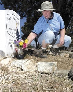 Courier/Nathaniel Kastelic Jo Boeckler, Yavapai Cemetery Association volunteer, places flowers Saturday morning beside a new headstone, installed by Veterans Affairs, in Citizens Cemetery in preparation for the Memorial Day observance.