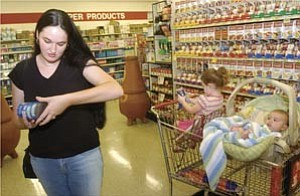 Courier/Les Stukenberg Jasmine Demaline with her 2-year-old daughter Shareesa looks at a brochure of WIC-approved products as she shops at Basha¹s at the Frontier Village in Prescott Friday afternoon.