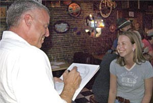 Courier/Cindy Barks On his quest to draw the faces of 1,000 people in downtown Prescott, Brian Lemcke sketches local resident Terri Christensen Friday night at Coyote Joe¹s on Montezuma Street. Lemcke also sketched the drawings above this photo.