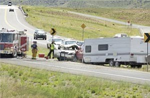 Courier/Nathaniel Kastelic  Central Yavapai Firefighters and Prescott Valley Police officers stand near the wreckage of a two vehicle accident on Fain Road and Lakeshore Drive exit Sunday in Prescott Valley.