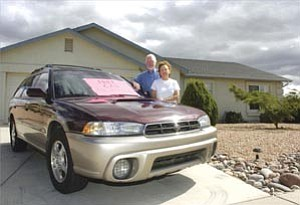 Rich and Jeanne Darrow stand next to the 1999 Subaru they are including as an incentive to the buyer of their Prescott Valley home. The Darrow¹s, unlike many others, plan to move back to California to be closer to family.  Courier/Les Stukenberg