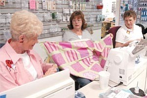 Jill Batcheler, center, shows a quilt she is working on as Pat Silvernell, left, and Rita Markowicz work on projects for cancer patients Friday afternoon.   Courier Photo/Jo. L. Keener