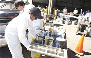 Courier/Nathaniel Kastelic Allen Fernandez, front left, and Ramsey Thompson, both with Prescott Fire Crew 7, unload paint and oil from a vehicle at the free household hazardous waste collection day at the Prescott Transfer Station Sunday.