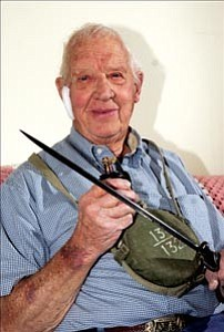 Ray Griffith of Prescott displays artifacts he returned home with after surviving the battle of Iwo Jima in World War II. Griffith has a Japanese canteen, a rifle bayonet and deactivated hand grenade.  Courier Photo/Jo. L. Keener