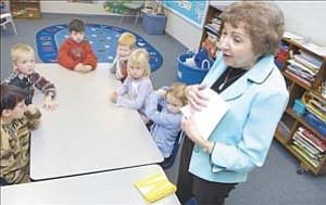 Courier/Nathaniel Kastelic Carol Stimple, pre-kindergarten teacher, shows her students how to create an ³M² book at American Lutheran School in Prescott Monday.