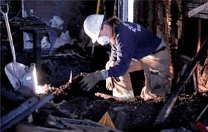 Courier/Les Stukenberg  City of Prescott Fire Investigator Kristi Gagnon looks for the cause of the early Monday morning fire in the charred remains in the living room of the house in a 300 block of East Gurley Street. Three Prescott engines and one Central Yavapai Fire District engine responded to the scene.