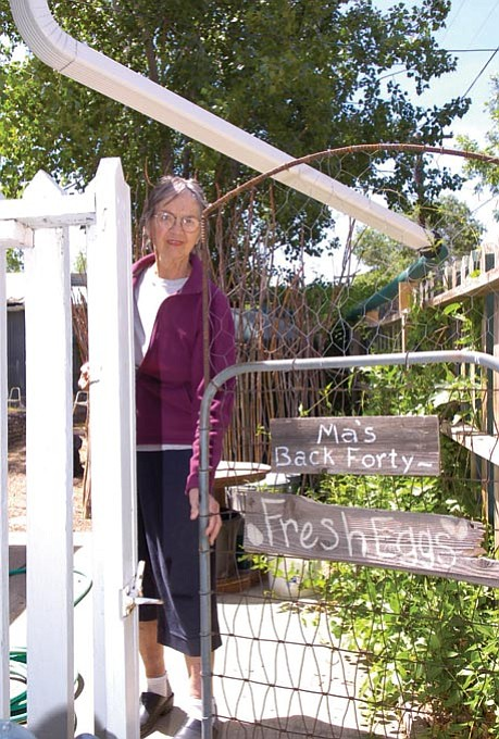 The Daily Courier/Jo.L. Keener --- Carol Oldershaw stands in her garden and chicken coop, where all garden watering is done from collection tanks. The rain runoff from the roof flows into a storage tank at the rear.