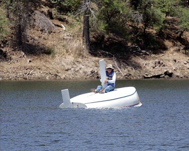 Courier photo/Les Stukenberg --- Robert Andrus of Chino Valley sits atop his overturned sailboat on Lynx Lake Thursday afternoon.