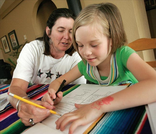 The Daily Courier/Les Stukenberg Coyote Springs Elementary School teacher Julie Miller tutors neighbor Brooke Cherry on her math skills Monday afternoon. Cherry will be attending 2nd grade at Liberty Traditional School in the fall, and her parents felt she needed help with her math skills.