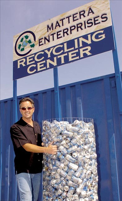 The Daily Courier/Jo. L. Keener Joe Mattera moves a container of recycled beverage cans at his Prescott Valley recycling location Thursday.