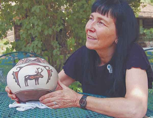 The Daily Courier/Joanna Dodder Sandy Lynch, Curator of Anthropology for the Sharlot Hall Museum in Prescott, holds a piece of high-quality contemporary Zuni pottery. Zuni potters are common victims of fraudulent art, she said.