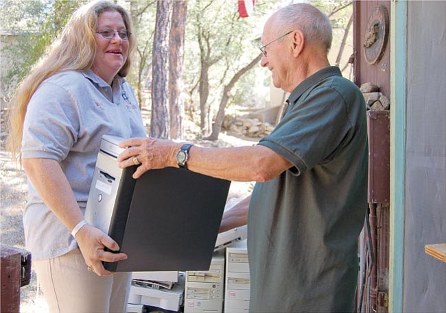 Bruce Stull, coordinator of Computer Literacy Resources, gives Nora Jenkins, Prescott Head Start kitchen manager, a free computer for her organization as part of his non-profit group's services. This was the 500th device Computer Literacy Services has given away to date.
