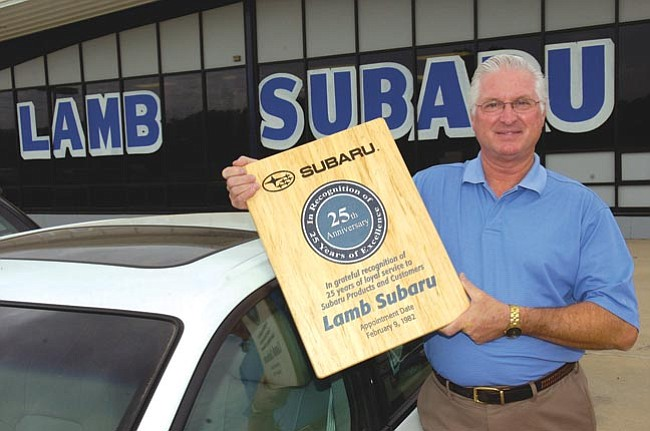 The Daily Courier/Jo. L. Keener  Larry Strole, general manager of Lamb Subaru displays a plaque awarded to the dealership after 25 years of service and sales, Friday, in Prescott.