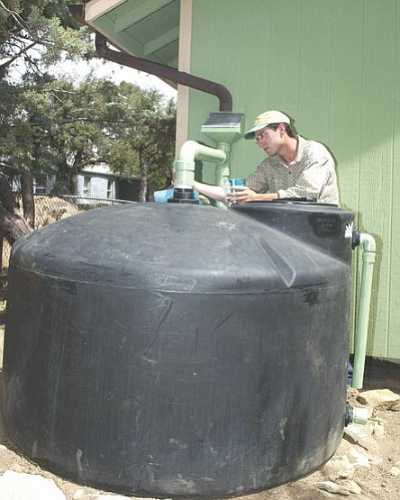 TCBN/Nathaniel Kastelic ---  MacRae Nicoll, owner of High Desert Rain, puts a second coat of paint on a 550-gallon rainwater catchment system at a Prescott home.