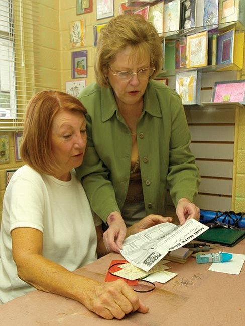 Saundra Martin, left, and Sandy Louttit of Sandy's Corner review instructions during a Saturday morning book class.
