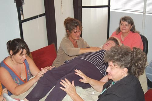 Ann M. Martin,  at the head of the table, Simone Lambros, Jennifer Spurr and Linda Stevens practice Reiki on Wini Daniel. Lambros is a Reiki practitioner who recently moved from New Mexico to Prescott and is a members of the PHAA.