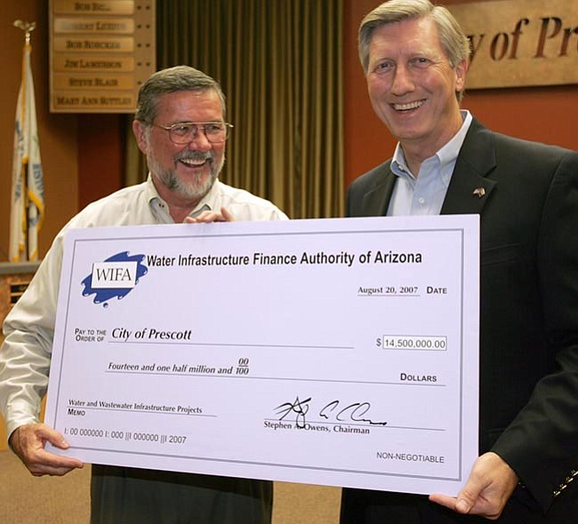 The Daily Courier/Les Stukenberg <br>Prescott Mayor Rowle Simmons accepts a ceremonial check for the loan of $14.5 million from Water Infastructure Finance Authority of Arizona Chairman Steve Owens during a ceremony at City Hall on Monday. 9.8 million dollars of the loan will be used for several drinking water projects and $4.7 million for sewer upgrades around the Prescott area.
