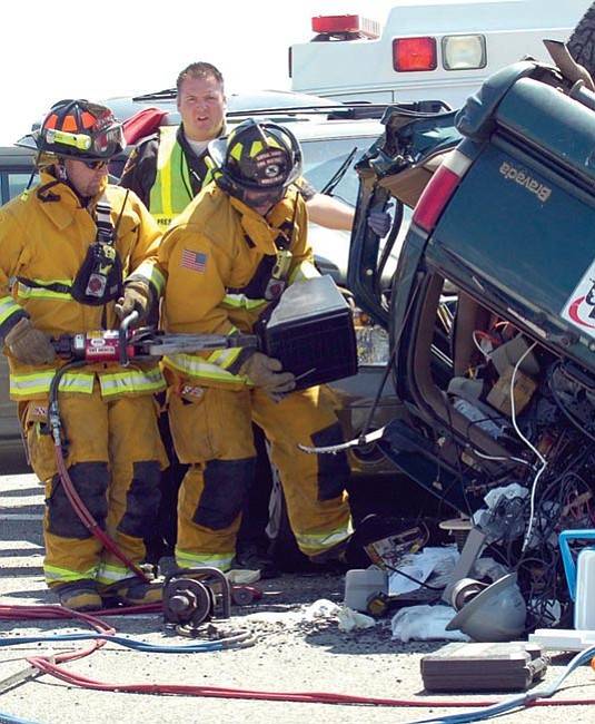 Central Yavapai Fire District firefighters use pneumatic tools as they work to extricate a driver from this overturned vehicle Sunday morning near the intersection of Fain Road and Highway 69 in Prescott Valley.