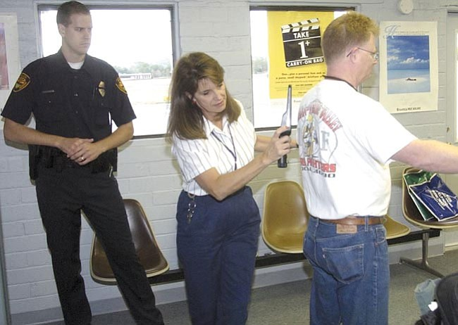 "Prescott police officer Paul Clemens watches as Bobi Cronin ""wands"" David Marshall in this 2002 file photo taken at Prescott's Ernest A. Love Field."