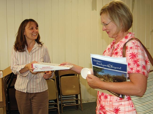 The Daily Courier/Joanna Dodder Crystal Frost, left, of the state's Prescott Active Management Area office hands out free rain gauges at Monday's Yavapai County Local Drought Impact Group meeting.