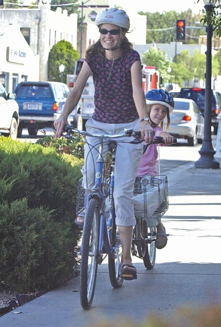 Lisa Barnes and her daughter, Aless D'Alosio, 6, bike home from Mountain Oak School and ride on the sidewalk for a short distance to avoid the busy intersection of Sheldon and Montezuma streets in Prescott Monday afternoon.  The Daily Courier/Nathaniel Kastelic