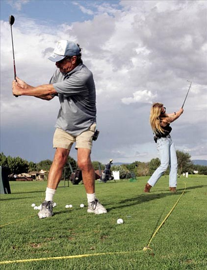 The Daily Courier/Les Stukenberg R. Stiles and Kathleen Twomey hit golf balls Wednesday afternoon on the driving range at the City of Prescott's Antelope Hills Golf Course.
