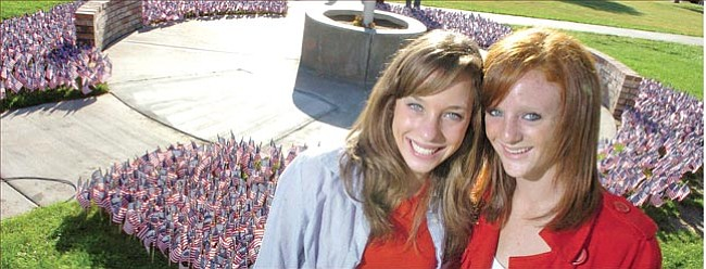 The Daily Courier/Nathaniel Kastelic Brandi Heuer, left, and Dawn Heuer, both 15-year-old sophomore students at Prescott High School, pose Tuesday in front of the 2,977 American flags they placed around the flagpole to remember and honor the victims of Sept. 11, 2001.