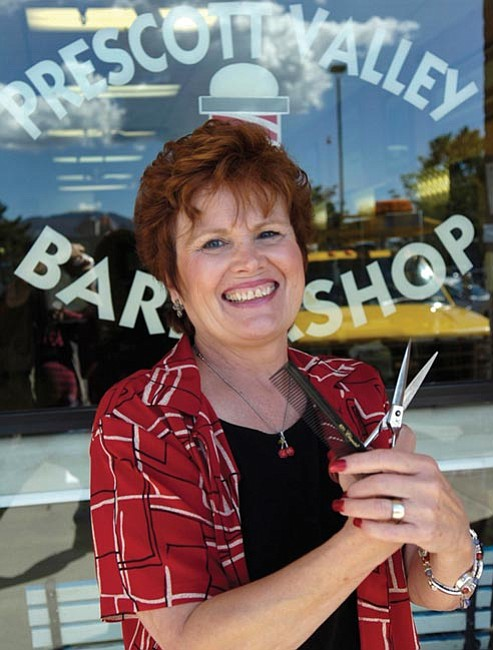 The Daily Courier/Jo. L. Keener  Debby Waugh of Prescott Valley Barber Shop poses outside her shop where she has cut hair for over 19 years.