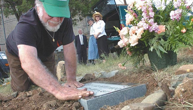 The Daily Courier/Nathaniel Kastelic Yavapai Cemetery Association volunteer Richard Swope installs Lucy Lake Pettit Hand's new headstone at Citizens Cemetery in Prescott Sunday as Lucy's great-granddaughter Fae Houck, right, watches. With Fae is her husband Chuck and YCA President Pat Atchison.