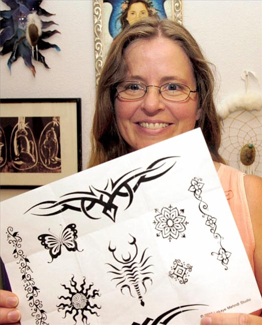 Dana Cummins, a henna tattoo artist, displays a sample of designs Thursday afternoon. Henna tattoos will fade away after about three weeks and is not permanent.  The Daily Courier/ Jo. L. Keener