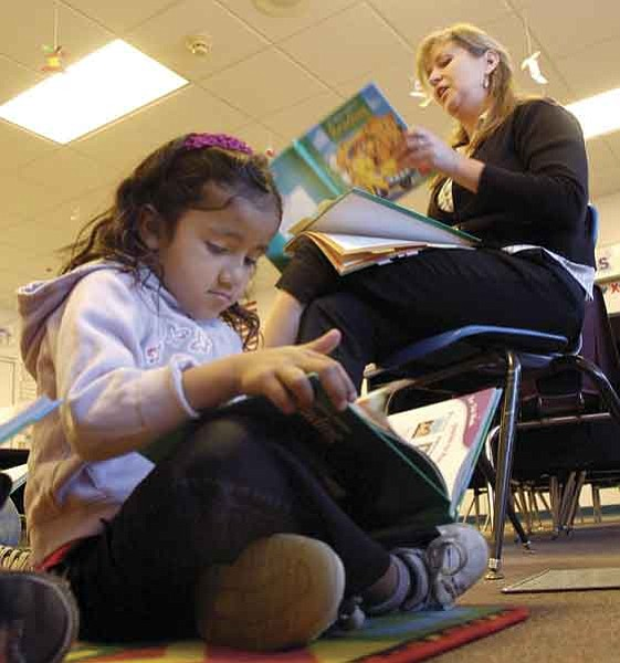 The Daily Courier/Jo. L. Keener  Iris Cardiel reads from a book Tuesday during Sarah Langham's first-grade reading program at Prescott Valley's Lake Valley Elementary School. The Reading First program supplies schools with money for professional reading development.