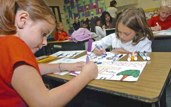 Kaity Browning, left, and Kate Annibale work on their illustrations to accompany their writings in Danette Derickson's first-grade classroom at Liberty Traditional School in Prescott Valley Monday.