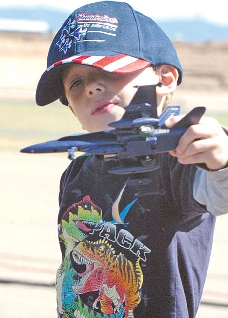 The Daily Courier/Nathaniel Kastelic Zachary Amstutz, 5, plays with a toy airplane and watches the Arizona Sky Fest Air Show at Ernest A. Love Field in Prescott Saturday.