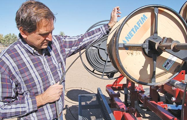The Daily Courier/Doug Cook Chino Valley farmer Norm Freeman draws down a piece of specialized black plastic tape that is used for drip irrigation systems, including the one on his farm.