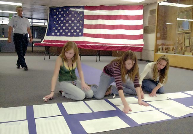 Prescott High School students, from left, Rhea Nanni, Jessica Canes and Haley Hughes work to make a list of their own veterans memorial wall at Prescott High School Thursday afternoon. The exhibit will be open to the public through Wednesday.