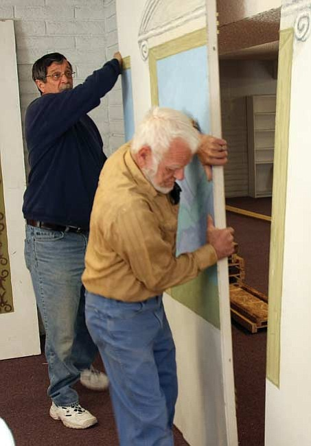 The Daily Courier/Les Stukenberg Volunteers James MacDonald, left, and Joe Watkins move one of the dividers as they start setting up the first Prescott Area Winter Shelter for women and women with children at the Hillside Church of God on Ruth Street in Prescott.