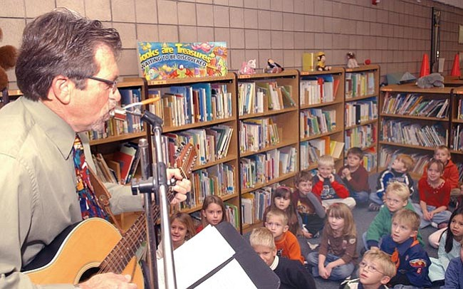 The Daily Courier/Jo.L. Keener  Abia Judd Principal Larry Peterson entertains first-grade children after trimming a tree at the school Tuesday morning.
