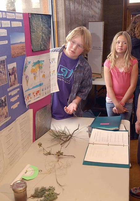 The Daily Courier/Jo.L.Keener  Derek Parker, left, and Shyann O'Brien stand by their display presentation Thursday morning at Prescott College. The Skyview school students studied Prescott's biotic communities and presented their findings at Prescott College. Parker's and O'Brien's work centered on the growth of the forest and the chaparral.