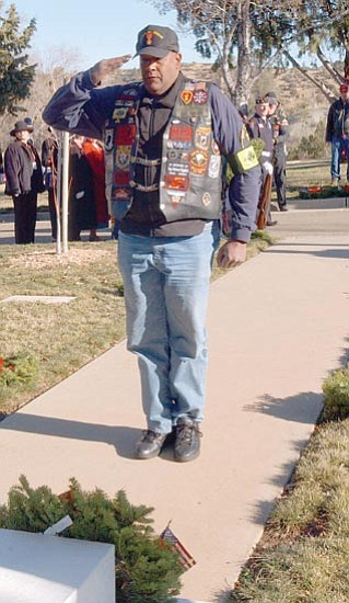 Daryl Neil, of Phoenix, salutes after laying a wreath at the grave of Prescott's Unknown Soldier during the Saturday morning Wreaths Across America event. <br> The Daily Courier/Jo.L.Keener