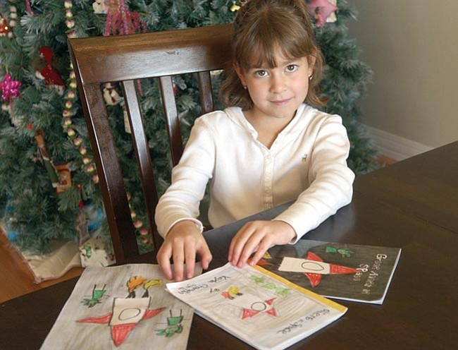 """The Daily Courier/Jo.L. Keener Kayla Champlin, 7, reveals her first published book """"Green Aliens in Space"""" which will soon be available at the Prescott Library."""