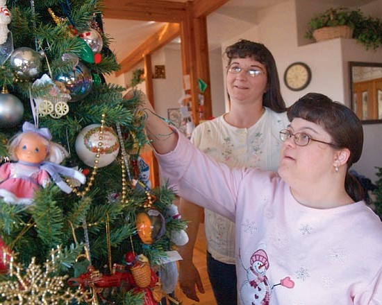 The Daily Courier/Jo.L.Keener  Ashley Millsap, right, and her mother Marie decorate a Christmas tree in their Chino Valley home. Ashley, who lives with Down syndrome, tries to do everything that her friends and family do.