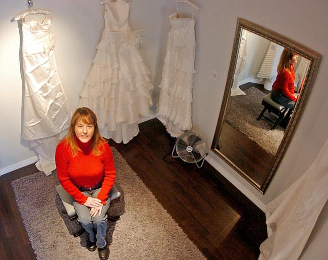 The Daily Courier/Matt Hinshaw<br> Janie James-High, co-owner of Ciao Bella Bridal and Eveningwear Salon, sits in the dressing room in front of a display of wedding gowns at her store in Prescott on Monday morning.