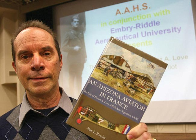 The Daily Courier/Les Stukenberg<br> Alan Roesler holds up a copy of his book about Ernest Love, whose name the Prescott Airport bears, before speaking at Embry-Riddle Aeronautical University in Prescott.