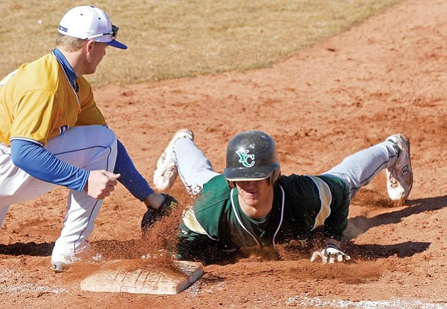 The Daily Courier/<br>Matt Hinshaw<br>The basepaths were a busy place at Roughrider Park on Wednesday. Yavapai's Erik Knutson slides in just under the tag of Salt Lake first baseman Sean Moysh during YC's 13-12 victory.