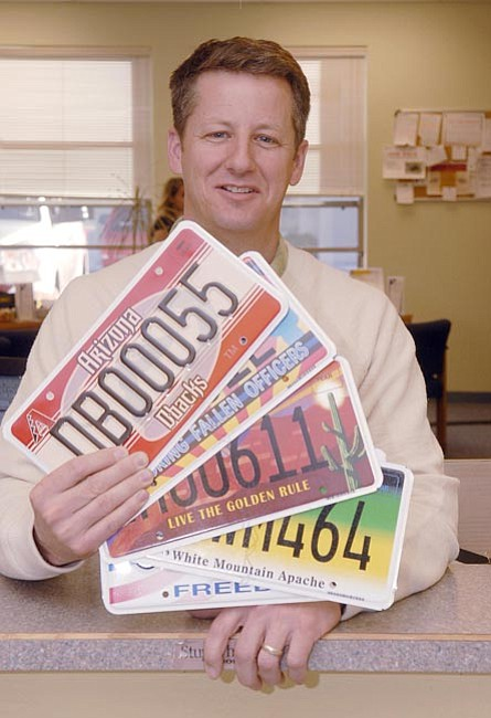 The Daily Courier/ Jo. L. Keener<br> Ken Foote, owner of FooteWork, a private motor vehicle office, displays a selection of Arizona license plates Wednesday afternoon.