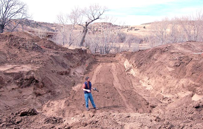 The Daily Courier/Doug Cook<br> Prescott Creeks Executive Director Michael Byrd stands in a manmade ditch where his non-profit group and others, including a crew from the City of Prescott, are reconstructing a storm water basin to better  protect the Watson Woods Riparian Preserve from erosion.