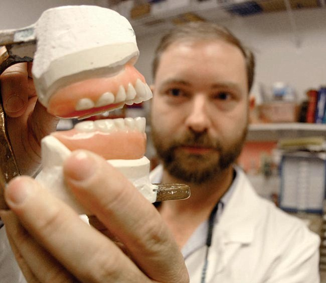 The Daily Courier photos/Jo. L. Keener<br> Dr. Joel J. Nichols displays a set of dentures Thursday morning in his Prescott Valley office lab. Nichols is one of a very few dentists that make their own prosthetics.