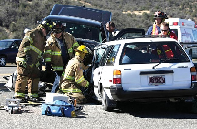 The Daily Courier/Les Stukenberg<br> Emergency personnel work to free the occupants of two vehicles in this three-vehicle collision on Highway 69 just west of Prescott Lakes Parkway Friday morning.