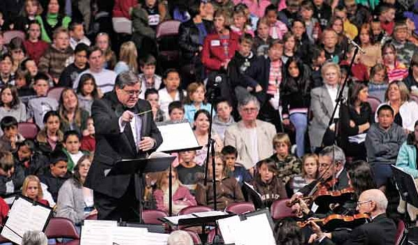 The Daily Courier/Jo. L. Keener<br> Director Paul Manz conducts the Prescott Pops Symphony Orchestra at Tim's Toyota Center Wednesday morning. The concert, sponsored by The Daily Courier, had 3,500 area children from Yavapai County schools in attendance.