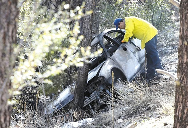 The Daily Courier/Les Stukenberg<br> Central Yavapai Fire Marshal Charlie Cook looks into the burned vehicle that holds the remains of a woman. The single-vehicle accident happened in the Highland Pines subdivision northwest of Prescott Wednesday afternoon.